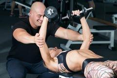 Pesos de levantamento da mulher com seu instrutor pessoal no gym Imagem de Stock