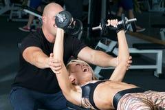 Pesos de levantamento da mulher com seu instrutor pessoal no gym Foto de Stock