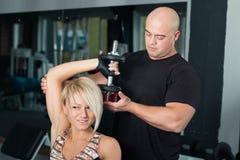 Pesos de levantamento da mulher com seu instrutor pessoal no gym Foto de Stock Royalty Free
