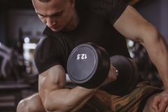 Pesos de levantamento do halterofilista masculino no gym fotos de stock