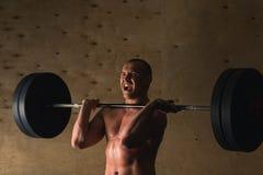 Pesos de levantamento do homem Exercício muscular do homem no gym que faz exercícios com barbell foto de stock