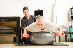 Pesos de levantamento do paciente ao encontrar-se na bola do exercício por físico fotos de stock royalty free
