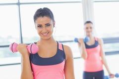 Pesos de levantamento do peso da mulher apta com o amigo no fundo no gym imagens de stock royalty free