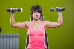 Pesos de levantamento do peso do treinamento da força da mulher do Gym no exercício da imprensa do ombro Exercício fêmea da menin fotos de stock