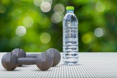Pesos e opinião lateral da garrafa de água no assoalho de alumínio no fundo borrado do bokeh Foto de Stock Royalty Free