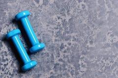 Pesos feitos do plástico azul ciano no fundo cinzento da textura fotografia de stock royalty free