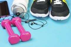 Pesos, garrafa do esporte, fones de ouvido e tênis de corrida cor-de-rosa na esteira do esporte Imagem de Stock Royalty Free