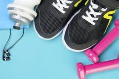 Pesos, garrafa do esporte, fones de ouvido e tênis de corrida cor-de-rosa na esteira do esporte Foto de Stock