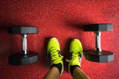 Pesos no gym com os pés do homem que vestem sapatas do esporte imagem de stock