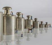 Pesos para la balanza con los trabajadores miniatura Foto de archivo libre de regalías