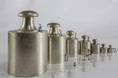 Pesos para la balanza con los trabajadores miniatura Imágenes de archivo libres de regalías