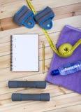 Pesos, pesos, toalha, água, caderno Imagem de Stock Royalty Free