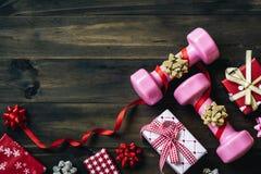 Pesos, presentes, e curvas cor-de-rosa do esporte no fundo de madeira, Merr Imagem de Stock Royalty Free