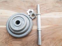 Pesos que treinam, dumbells do ferro com a placa no CCB de madeira velho da tabela Imagem de Stock