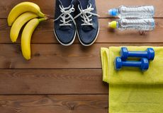 Pesos toalha e garrafa das sapatilhas da água na tabela de madeira Imagens de Stock
