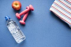 Pesos, uma garrafa da água e uma maçã com uma toalha do gym Foto de Stock