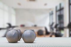 Pesos velhos no assoalho de alumínio da textura no fundo borrado do gym Fotografia de Stock