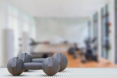 Pesos velhos no assoalho de alumínio da textura no fundo borrado do gym Imagens de Stock
