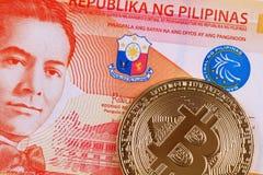 Pesosedel för tjugo filippin med en guld- bitcoin royaltyfria foton