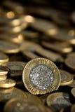 Pesosmynt för mexikan 10 i förgrunden, med många mer mynt i bakgrunden Arkivfoton