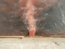 Pesque águas residuais de derramamento da tubulação da efluência da fábrica com sangue e entranhas de peixes processados no mar Imagem de Stock