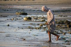 Pesque al vendedor hacia fuera que cruza la playa en la puesta del sol Foto de archivo libre de regalías