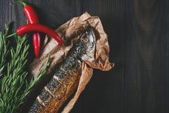 Pesque con romero en el documento de pergamino sobre un fondo de madera negro, comida sana en la opinión de sobremesa de la cocin fotografía de archivo