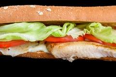 Pesque el bocadillo con pan de la lechuga del tomate y de iceberg del salvado, aislado en fondo negro Foto de archivo