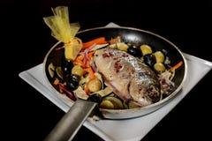 Pesque el gilthead preparado en un sartén con las verduras para a Imagen de archivo