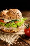 Pesque la hamburguesa con la carne de la caballa, el queso y las verduras frescas Fotografía de archivo libre de regalías