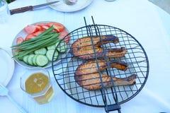 Pesque o cozimento no fogo com tomates e pepinos Foto de Stock