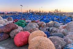 Pesque a rede e barcos de pesca de madeira azuis no porto, Essaouira, Marrocos Fotografia de Stock Royalty Free