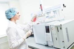 Pesquisador científico fêmea que põe a garrafa na cromatografia de gás fotos de stock royalty free