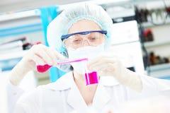 Pesquisador científico médico fêmea que guarda a garrafa Imagens de Stock