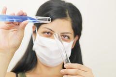 Pesquisador fêmea químico novo que guardara dois tubos de vidro Fotografia de Stock Royalty Free