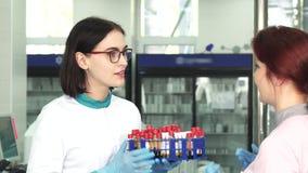 Pesquisador fêmea que entrega amostras de sangue a seu colega vídeos de arquivo