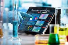 Pesquisador que trabalha com relatório da análise de dados na tabuleta digital o fotografia de stock