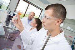 Pesquisadores novos no projeto de investigação da ciência no laboratório imagens de stock