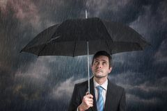 Pessimistic businessman with black umbrella in storm. royalty free stock images