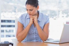 Pessimistic businesswoman sitting at her desk. In her office Stock Photos