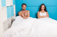 Pessimistic couple having an argument sitting on bed. Pessimistic couple having an argument in the bed Stock Photo