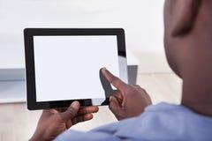 Pessoa africana que senta-se com tabuleta digital fotografia de stock