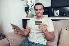 A pessoa alegre guarda o cartão de crédito e a tabuleta dos usos imagem de stock