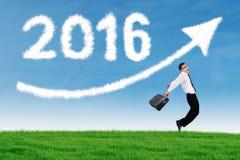 A pessoa alegre salta no campo com números 2016 Fotografia de Stock Royalty Free