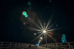 Pessoa anônima que senta-se em trilhos na ponte na noite imagem de stock