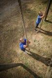 Pessoa apta que escala para baixo a corda durante o curso de obstáculo foto de stock