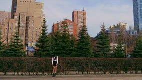 A pessoa asi?tica olha a c?mera perto da cidade e do parque Os povos est?o rindo e est?o sorrindo video estoque