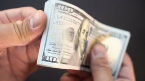 A pessoa considera o dinheiro com suas mãos um close-up Dólares no close up 4k do braço filme
