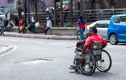 Pessoa da cadeira de rodas no meio da estrada fotografia de stock