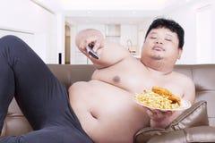 A pessoa da obesidade olha a tevê em casa Foto de Stock